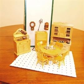 Kitchen Dollhouse Furniture: A collection of wooden kitchen dollhouse furniture. This collection includes a table with four chairs, a small sideboard, a kitchen hutch, icebox, tile flooring, and accessories. The pieces are unmarked.