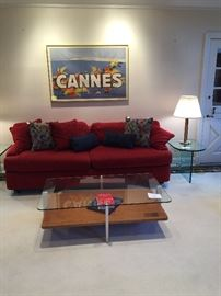 Glass and wood coffee table.  Red upholstered sofa in great condition.  End table is by Pace and lamp is one of a pair by Walter Von Nessen.