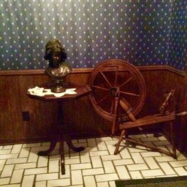 Antique spinning wheel. Center-side Table with girl bust.