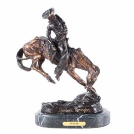 "Bronze Tone Reproduction Sculpture After Fredric Remington ""Outlaw"": A bronze tone reproduction sculpture after an original work titled Outlaw by Frederic Remington. The work depicts a cowboy riding a bucking horse. The piece is signed in-mold and embellished with gold tone ink near the base. The sculpture is mounted on an oval gray marble base with felt padding affixed to the underside."