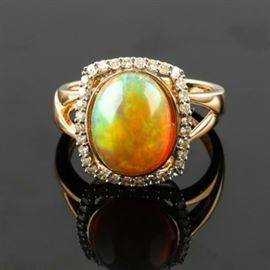 14K Yellow Gold Opal and Diamond Ring: A 14K yellow gold opal and diamond ring. This ring features a center oval cabochon opal set with a rectangular border of diamonds atop a split shoulder band.