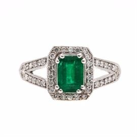 18K White Gold Emerald and Diamond Ring: An 18K white gold emerald and diamond ring. This ring showcases a center emerald surrounded by round brilliant cut diamonds. Round brilliant cut diamonds also accent the split shoulders.