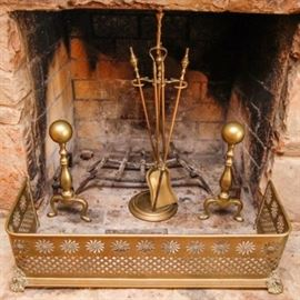 Vintage Brass Fireplace Accessories: A group of brass fireplace accessories. Included is a pair of brass tone andirons, a fireplace guard, and a set of fireplace tools. The pieces are each composed of brass and the guard features an open slit floral pattern throughout.