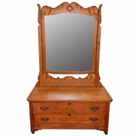 Vintage Victorian Style Oak Chest of Drawers with Mirror: A vintage Victorian style oak chest of drawers with mirror. This piece features a rectangular top chest with molded trim overhanging two full width, stacked drawers with brass escutcheon and decorative handles terminating on casters. Also includes a rectangular mirror with oak frame featuring applied scrolling acanthus leaf detail. There are no visible maker's marks.