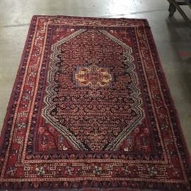 Hand-Knotted Persian Bijar Area Rug: A hand-knotted Persian Bijar area rug. This wool rug is hand-knotted in a palette of scarlet red, indigo, sky blue, coral, white, golden tan, and cerulean. It has an eight pointed star medallion on a hexagonal lozenge patterned with a geometric herati motif. The corner spandrels have boteh and vine designs and the rug is framed with squared meander and rosette borders. It has overcast selvedges and fringe to either end.