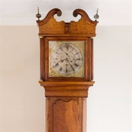 Vintage Wood Grandfather Clock: A vintage wood grandfather clock. The clock has a wood case with a golden oak finish and features swan pediments on the bonnet with spire finials. The case has reeded side columns with gold-tone caps flanking a glass front door that displays a silver-tone face with etched floral designs and a seconds and minute clock with black hands. Other features of the face include black Roman numerals and hands, two key arbors and raised brass scrollwork spandrels. The clock has a lower wood door with a brass pendulum and weights with chains and a plinth style base with bracket feet.
