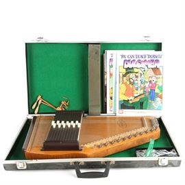 Oscar Schmidt Autoharp, Case and Instructional Songbooks: An Oscar Schmidt autoharp with a solid wood frame and a felt-lined hardshell case. A collection of instructional songbooks is included.