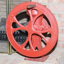 "Large Red Cast Iron Coffee Grinder: A large cast iron coffee grinder. The coffee grinder features a red finish to the cast iron construction and a wooden handle to the crank. It is marked ""No. 8"" to the wooden handle and has a canister to the background and rests on a flared base."