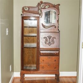 Antique Side-by-Side Late Victorian Bookcase Secretary: An antique late Victorian side-by-side secretary and bookcase. This unique piece is crafted from oak and has a carved, organically shaped crest to the top with scrolled detailing over a framed mirror. The right side of the cabinet has a pull down secretary desk top with writing surface and interior storage cubbies over three additional drawers below. The left side of the cabinet features a narrow curio with a bowed, glass paneled door that opens to three floating shelves for display or books. The piece has a caster feet and and is unmarked.
