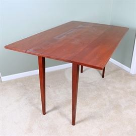 Cherry Drop-Leaf Dining Table: A narrow cherry drop-leaf dining table. This rectangular table features two long side drop-leaves over square tapered legs. No discernible maker's mark.