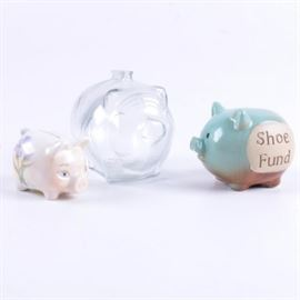 "Ceramic and Glass Piggy Banks: A collection ceramic and glass piggy banks. This collection includes a ceramic pig shaped coin bank marked ""Shoe Fund"", a ceramic pig shaped bank with hand painted flowers, and a glass pig shaped bank. There are three items in total."
