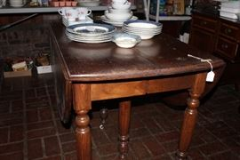 Walnut drop-leaf Victorian table with porcelain casters and 4 walnut leaves and center support leg