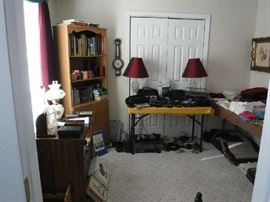 Some electronics, a few books and cds with a smattering of linens grace this middle bedroom.