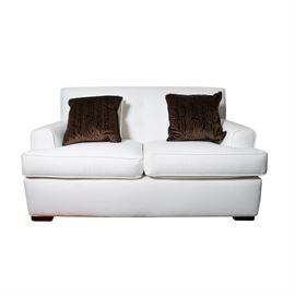 White Loveseat with Accent Pillows: A white upholstered love seat. This contemporary piece has a button tufted back, two removable seat cushions, squared sides and armrests, and apron. It is upholstered and piped in white fabric throughout, and sits on recessed block feet. It comes with four square throw pillows; two match the love seat, and two are brown and textured.