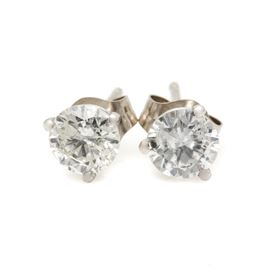 14K White Gold 0.75 CTW Diamond Earrings: A pair of 14K white gold stud earrings each featuring a diamond centerpiece.