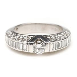 18K White Gold 1.97 CTW Diamond Ring: An 18K white gold 1.97 ctw diamond ring. This ring showcases a center tension set round brilliant cut diamond situated between baguette cut diamond shoulders. The sides of the ring are encrusted with round brilliant cut diamonds as well.
