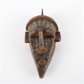 Marka Style Wood and Metal Mask: A Marka style mask from Burkina Faso made of carved wood covered in metal sheeting. The mask features narrow elongated facial features topped with a crest on the top of the head. Thin metal sheeting is affixed to the front of the mask. The piece is unsigned.