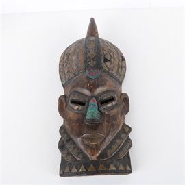 Ghanaian Style Carved Wood Mask: A Ghanaian style carved wood mask adorned with glass and copper accents. The mask is representative of a face with neck and head adornments. The piece is carved with slightly stylized facial features adorned with inset copper and colorful beaded adornments. The piece is unmarked.