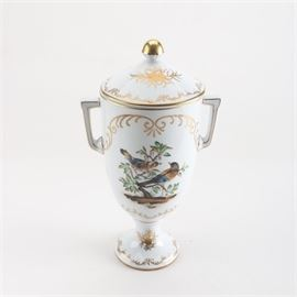 Antique Dresden Porcelain Lidded Urn: An antique Dresden porcelain lidded urn. This piece features an amphora style shape with a ball finial, angular handles, and a footed pedestal. It is decorated with a hand-painted scene of perched birds and finished with gilt filigree and trim throughout. The piece bears a blue underglaze crown mark to the base, which was used by many decorators between 1883-1893.