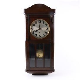 Kienzle Wall Clock: A Kienzle wall clock. The clock is cased in a medium finished wood with simple raised decor to the sides. The face is white with black Arabic numerals. The frame and pendulum are brass, the clock comes with the key.