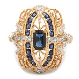 14K Yellow Gold Sapphire and Diamond Ring: A 14K yellow gold sapphire and diamond ring. The ring features a two-tone pierced filigree setting with milgrain detailing, having an emerald cut blue sapphire center stone with sapphire and diamond accents.