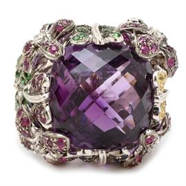14K White Gold Amethyst Gemstone and Diamond Statement Ring: A 14K white gold amethyst, gemstone and diamond statement ring. The ring features a checkerboard cushion cut amethyst center stone with diopside, synthetic ruby, synthetic blue and yellow sapphires and diamond floral accents.