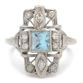 Vintage Platinum Blue Topaz and Diamond Ring: A vintage platinum blue topaz and diamond ring. This ring features a square blue topaz center stone in a pierced setting with diamond accents and milgrain detailing.