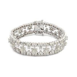 14K White Gold 16.00 CTW Diamond Statement Bracelet: A 14K white gold 16.00 ctw diamond statement bracelet featuring an open floral motif with scalloped link borders. The bracelet contains two-hundred and thirty-eight prong and channel set diamonds.