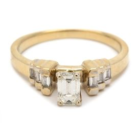 18K Yellow Gold Emerald Cut Diamond Ring: An 18K yellow gold emerald cut diamond ring. This ring has an emerald cut diamond center stone with stepped baguette diamond accents to the shoulders.
