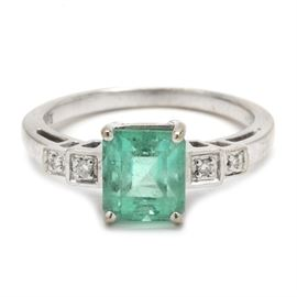 18K White Gold Emerald and Diamond Ring: An 18K white gold emerald and diamond ring. This ring features an emerald center stone flanked by four diamond accents to the shoulders.