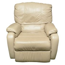 Leather Recliner: A leather recliner. This recliner features a light beige leather upholstery. The lever to recline is located on the lower right side of the chair. There are no evident tags or markings.
