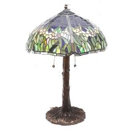 Faux Stained Glass and Bronze Table Lamp: A faux stained glass and bronze table lamp. This piece features a shade of acrylic resembling floral stained glass in a palette of blue, greens, yellow and neutral colors. There are two light bulb sockets within, and the shade hangs over a bronze tone cast metal base resembling a tree trunk with a round base.