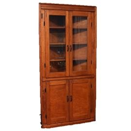 Antique Walnut Corner Cabinet: An antique walnut corner cabinet. This piece is constructed from walnut, and it features glass double doors, through which three triangular shelves can be viewed. The lower section has two cabinet doors which open to two shelves, and the cabinet also boasts hammered metal hardware.
