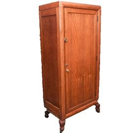 Antique Oak Wardrobe: An antique wardrobe. This piece is constructed from oak, and it features a quarter sawn oak door and frame to the front side. The door opens to spacious compartment with a curtain rod at the top. The wardrobe stands on squared cabriole feet with casters underneath.