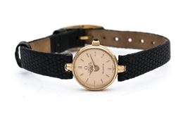 Omega Tiffany & Co. Wristwatch: An Omega Tiffany & Co. wristwatch with small round gold tone case and textured black leather band.