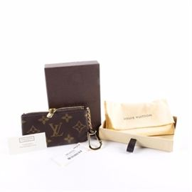 """Louis Vuitton Monogram Canvas Key Pouch: A Louis Vuitton Monogram key pouch. This purse has an LV logo printed coated canvas exterior with a gold tone key fob chain and a top zipper closure. It has a cross-grain leather interior and date code """"TA1115"""". A dust bag and box are included."""
