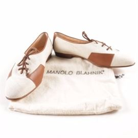 Manolo Blahnik Canvas and Leather Spectator Shoes: A pair of spectator style shoes from Manolo Blahnik. The lace up shoes, in size 37.5, feature beige canvas uppers, brown leather accent patches on the sides and counters, and leather piping trim on the throats and collars. The casual shoes, made in Italy, include brand labeling on the insoles, soles, and dust bag.