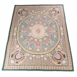 Handwoven Indian Wool Area Rug: A handwoven Indian area rug. This wool rug is chain-stitched in a palette of rose, sage, slate blue, beige, celadon, cream, forest green, and dusty pink. It features a neoclassical design beginning with an oval inner field with a floret medallion at the center amid palmettes, scrolling acanthus, flowers, and leaves. The inner field rests on a rectangular outer field, which is grounded in forest green and populated with a combination of diamond lattice patterns, scrolling acanthus, and palmettes cameos. The field is framed by compound borders including a primary border grounded in celadon and filled with pink and cream palmettes. Edges are serged on all sides under a full fabric backing. The rug is unlabeled.