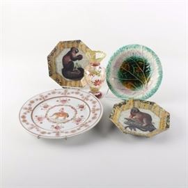 Signed John Derian Plates with Late 19th Century Victorian Majolica Plate: An assortment of tableware including a pair of signed John Derian plates. Each octagonal piece is decoupaged with a monkey on a ground of French text, finished with a colorful collage border. They are finished with black paint and gold tone trim to the underside, signed and dated. These are accompanied by a late 19th Century Victorian majolica plate. This leaf molded piece is decorated with an argenta palette to the well and a mottled brown glaze to the underside. It bears an impressed mark to the base and minor glazing imperfections indicating the piece was tripod fired during the last decade of the 1800s. A glass vase by Tracy Porter with hand-painted floral detail and an East Asian porcelain plate are also included. Each is marked with a label.