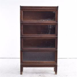 """Globe-Wernicke Vintage Oak Barrister Bookcase: A vintage oak barrister bookcase by Globe-Wernicke. The dark stained oak cabinet features four stacked shelves with rising cabinet doors, glass panes and brass knobs. The bookcase sits on squared legs with flat feet. Marked """"Globe-Wernicke Co. Sectional Book Case 110-299""""."""