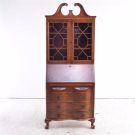 Vintage Mahogany Chippendale Style Secretary Desk: A vintage mahogany chippendale style secretary desk. This mahogany and mahogany veneer reverse serpentine fall front desk with bookcase has a broken arch pediment; with the upper cabinet having two glazed doors with an elaborate lattice design of lozenges and squares, enclosing two adjustable shelves. The front of the desk, which serves as the writing surface when down is fitted with nine drawers, a shell carved prospect door, as well as four pigeon holes; all above four long reverse serpentine drawers mounted with brass bat wing plates with bail pulls as well as bat wing escutcheons; all on a moulded reverse serpentine apron on short carved claw and ball feet. No apparent maker's mark.