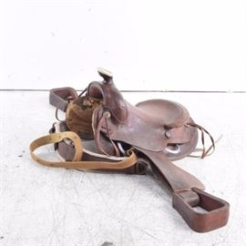 Leather Western Roping Saddle: A brown leather western roping saddle. This saddle shows a low and rounded pommel, thick horn, low cantle, round skirt, and wide stirrups. It features tooling to the skirt, fenders and stirrups and includes brass-tone conchos and leather stitching. A nylon cinch with faux sheepskin padding is additionally included.
