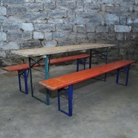 Vintage German Biergarten Picnic Set: A vintage German Biergarten picnic table and two benches. The rectangular tops of the seats are hardwood painted a bright orange tone, whereas the table's top is presented unfinished. The collapsible bases are blue painted metal hardware that folds down to flatten the items.