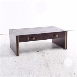 Leather Covered Coffee Table: A rectangular coffee table, with panel legs and two aligned drawers across the front. It is covered in dark brown leather with brushed gold tone metal bands inlaid at the edges. The drawers have leather strap handles.
