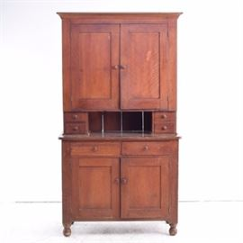 Antique Cherry Buffet and Hutch: An antique cherry buffet and hutch. The top, shelved cabinet has blind panel doors and sits over two small drawers on either side of a recessed open space. The top portion is stepped back over a bottom cabinet with two aligned drawers over blind panel doors, with interior shelving. The doors and drawers all have wooden knobs; drawers have hand-cut dovetails. The piece has unfinished vertical boards to the back, and stands on ball feet.