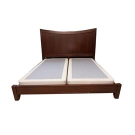 King Sized Bed Frame: A block shaped king sized bed frame. The bed frame features solid wood sides, a plywood headboard center, demi-lune curved top to the headboard. The bed frame rests upon block feet and has a simplistic apron to the front. Item is marked to the back with a warranty number.