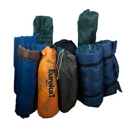 Grouping of Camping Equipment: A grouping of eleven pieces of camping equipment. This lot features two tents, two air mattresses, two self inflating mattresses, four folding chairs, and one sleeping bag. The tents are brand Coleman Sundome 7'x 7' and a Eureka Apex tent. The air mattresses feature navy blue colours with black straps for carrying. The self inflating mattresses are Therm-a-Rest brand one number reads '4729259' and the other reads ' 5112392'. There are four green folding chairs, two larger and two smaller. And one The NorthFace brand sleeping bag.