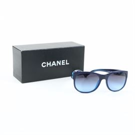 """Chanel 5182 CC Logo Sunglasses with Case and Box: A pair of 5182 Italian made sunglasses from Chanel. The designer eyewear features translucent navy blue frames, Wayfarer style rims with blue tinted lenses, and silver tone CC logos on the exterior temples.The right interior temple is marked """"Made in Italy B CE"""" and the left interior temple is labeled """"Chanel 5182 c.1218/4C 57-19 135 2N"""". The sunglasses are presented with a black quilted CC logo hard case and a brand labeled box."""