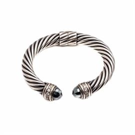 David Yurman Sterling Silver Hematite and Diamond Hinged Bracelet: A David Yurman sterling silver hematite and 0.40 ctw diamond hinged bracelet. This hinged bracelet features a twisted cable motif, which is capped on each end with a bullet faceted hematite, with diamond accents.