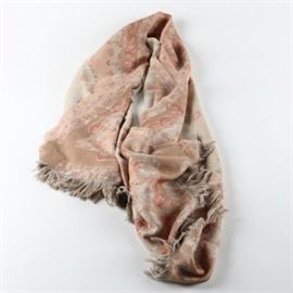 Moksha Floral Shawl: A Moksha floral shawl. This shawl has a tan center adorned with pink floral accents with varying pink hues of flora and fauna designs along the edge. It has fringe along the outside edge.
